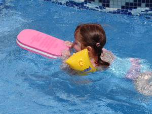 toddler swimming independently in armbands at Angela's Swim School